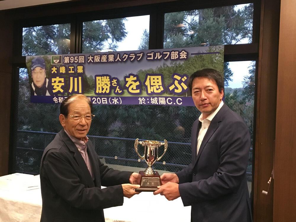 優勝したアジア化成工業所の高田英伸取締役(写真右)と、手渡す山口伊太郎ゴルフ部会長.jpg